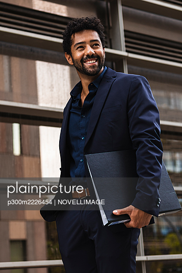 Confident entrepreneur with folder standing against building in city - p300m2226454 by NOVELLIMAGE