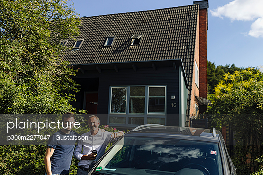 Smiling father and son standing by house near car during sunny day - p300m2277047 by Gustafsson