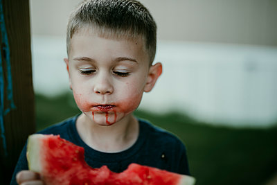 Boy with eyes closed eating watermelon - p1166m1489122 by Cavan Images