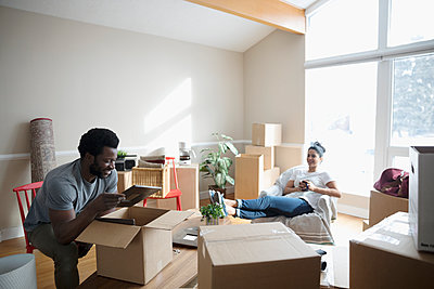 Young couple unpacking, moving into new home - p1192m1559947 by Hero Images