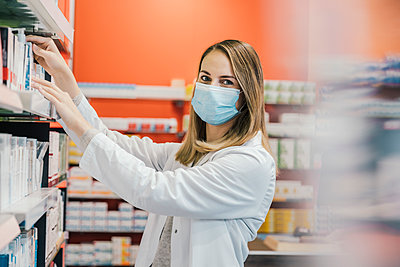 Pharmacist wearing protective face mask while working in chemist shop - p300m2243129 by Mareen Fischinger