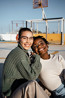 Friends smiling while sitting at basketball court - p300m2243343 by Rafa Cortés