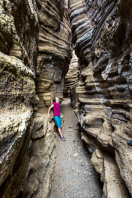 MONO LAKE, CA, USA. A young woman stands in the bottom of a narrow, deep slot canyon looking up at the striated rock walls. - p343m1167984 by David Hanson