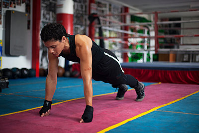 Female boxer doing planks in gym - p429m2050659 by Image Source