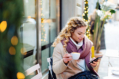 Woman using smartphone and having hot drink at cafe, Firenze, Toscana, Italy - p429m2075226 by Sofie Delauw