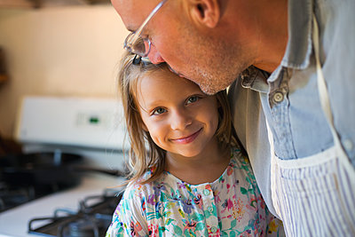 Portrait of girl being kissed on forehead by father in kitchen - p924m1557839 by Kinzie Riehm
