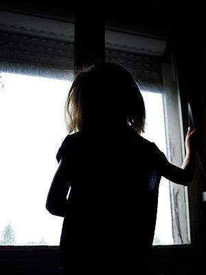 Mädchen schaut aus dem Fenster - p945m1467741 von aurelia frey