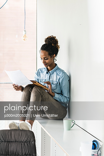 Young businesswoman sitting on shelf, using digital tablet, reading documents - p300m2005321 von Uwe Umstätter
