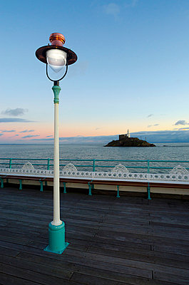 Victorian Lamp Post on Seaside Pier Looking at Lighthouse on Rock - p1072m1056651 by chinch gryniewicz