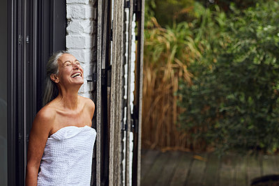 Cheerful mature woman wearing towel standing at doorway of house - p300m2241269 by Maya Claussen