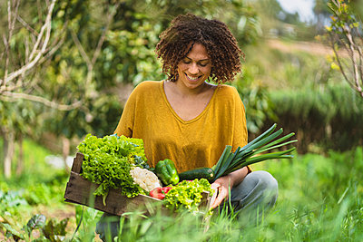 Smiling woman looking at vegetables in crate while squatting in garden - p300m2267348 by Steve Brookland