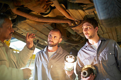 Two car mechanics with client in repair garage - p300m980966f by zerocreatives