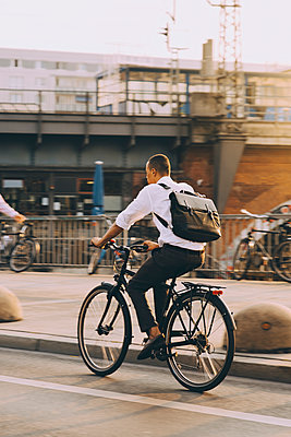 Rare view of male executive riding bicycle on street in city against sky - p426m2169603 by Maskot