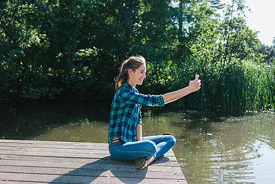 Junge Frau am Seeufer macht ein Selfie - p586m1064917 von Kniel Synnatzschke