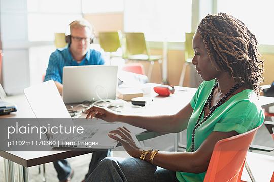 Profile of stylish businesswoman using laptop at shared desk.