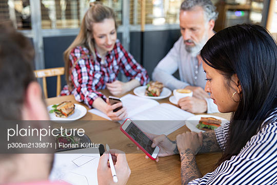 Casual business people having a meeting in a cafe - p300m2139871 by Florian Küttler