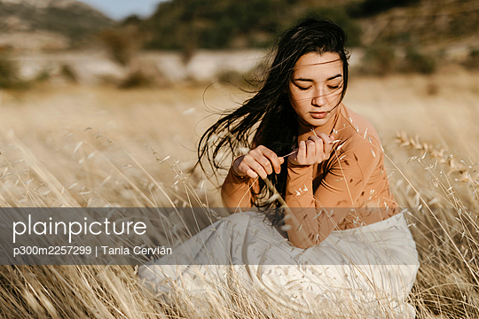 Young woman contemplating while sitting amidst gfrass in field during windy day - p300m2257299 by Tania Cervián