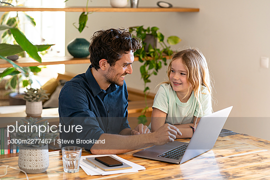 Happy father and daughter at home sitting at table in front of laptop looking at each other - p300m2277467 von Steve Brookland
