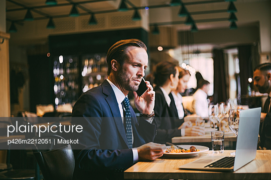 Male business person talking on phone while eating food in restaurant - p426m2212051 by Maskot