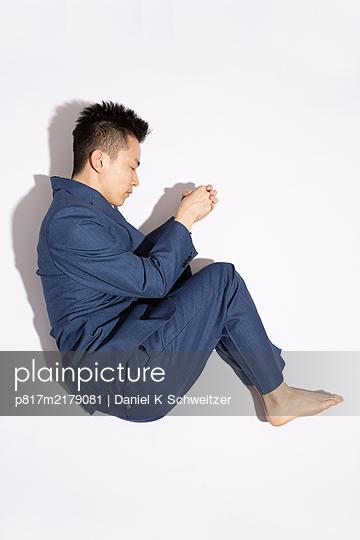 Asian man in pyjama against white background - p817m2179081 by Daniel K Schweitzer