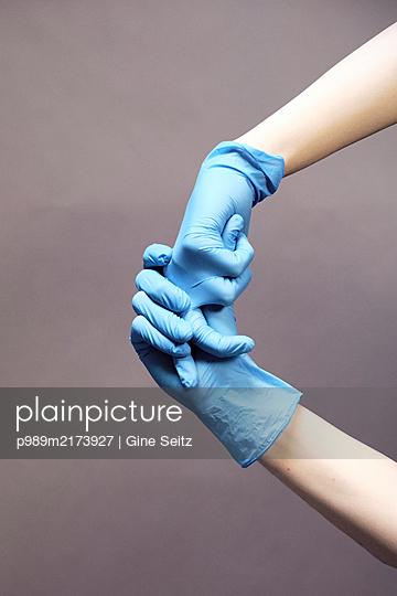 Gummihandschuhe anziehen - p989m2173927 von Gine Seitz
