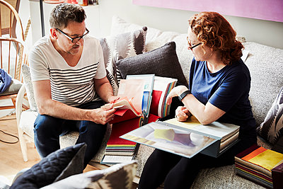 Two people, a man and woman sitting on a sofa, looking at a selection of fabric samples. - p1100m1177688 by Mint Images