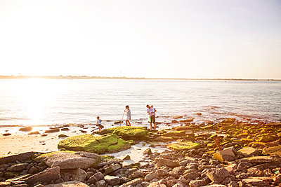 Family searching for clams at seashore against sky on sunny day - p1166m1096933f by Cavan Images