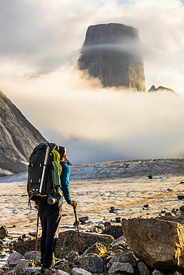 Backpacker looking up at the summit of Mount Asgard, Baffin Island. - p1166m2189678 by Cavan Images