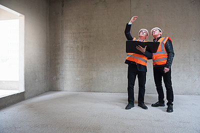 Two men wearing safety vests talking in building under construction - p300m1460674 by Daniel Ingold