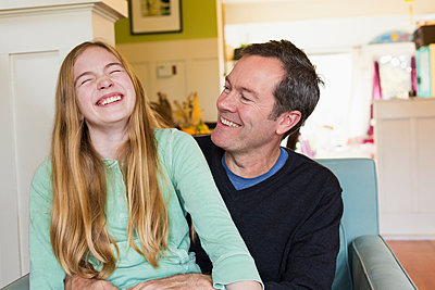 Caucasian father and daughter laughing in living room - p555m1459315 by Don Mason
