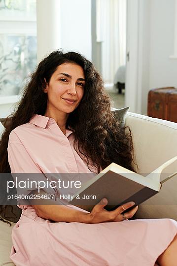 Frau auf der Couch hält ein Buch, Portrait - p1640m2254627 von Holly & John