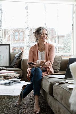 Portrait confident, happy female interior designer on living room sofa - p1192m2088250 by Hero Images