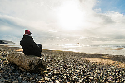 France, Bretagne, Finistere, Crozon peninsula, woman sitting on log on the beach - p300m1120760f by Uwe Umstätter