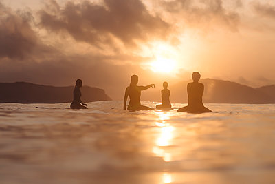 Indonesia, Lombok, group of surfers sitting on surfboards at sunset - p300m1568158 by Konstantin Trubavin
