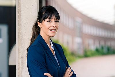 Smiling female entrepreneur by column at office park  - p300m2240825 by Joseffson