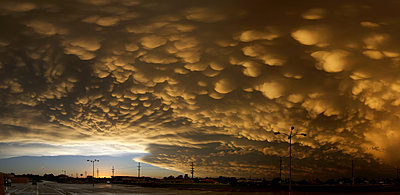 Panoramic image of orange mammatus clouds at sunset, following a day of tornadoes and severe storms, Dodge City, Kansas - p429m1181235 by Chris Kridler