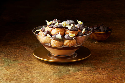 Still life with chocolate profiteroles on gold plate, christmas dessert - p429m2068611 by Danielle Wood