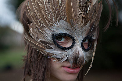 Young woman wearing a mask of feathers - p92411782f by Ariel Kay