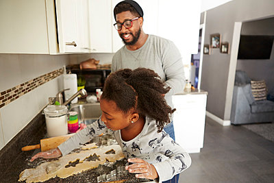 Father and daughter baking cookies together - p924m1224576 by Biz Jones