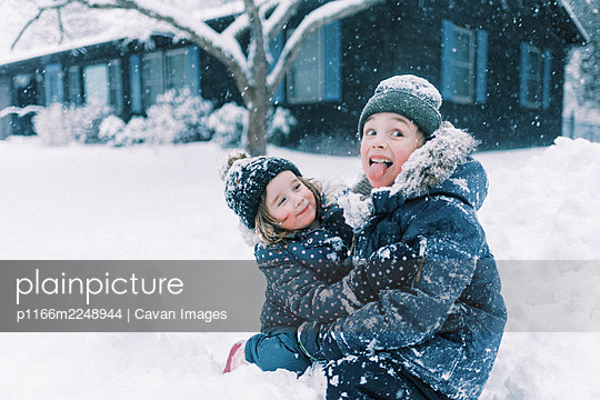 Two children hugging in snow and playing together in nor'easter storm - p1166m2248944 by Cavan Images