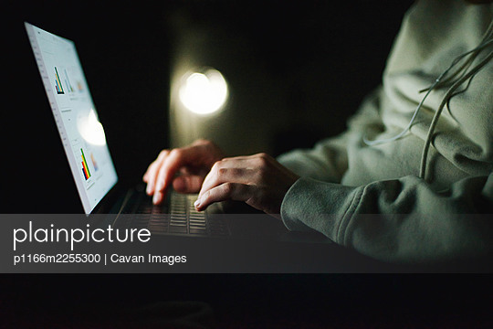 Anonymous woman working on laptop at night - p1166m2255300 by Cavan Images