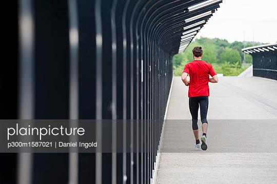 Rear view of man running on a bridge - p300m1587021 von Daniel Ingold