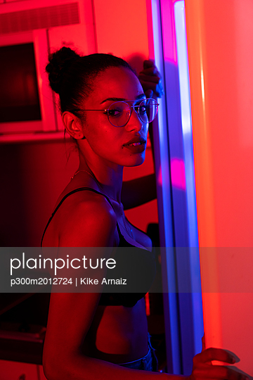 Portrait of beautiful young woman wearing bra and glasses in a dark illuminated room - p300m2012724 von Kike Arnaiz