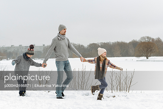 Father and two children walking in winter landscape - p300m2166871 by Ekaterina Yakunina