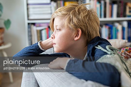 Bored boy on sofa - p312m2191239 by Malin Kihlström