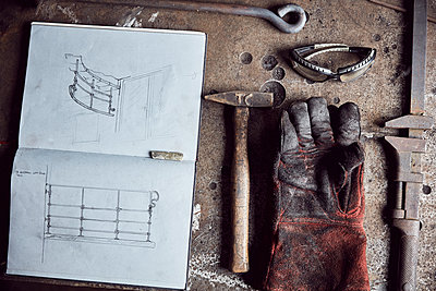 Still life of artisan metalworker's tools, sketches in a notebook and a blackened thick protective glove - p1100m2010437 by Mint Images