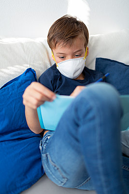 Boy with mask is in his room doing homework at home during the corona crisis - p300m2180704 by Epiximages