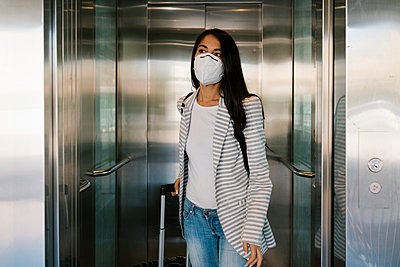 Woman wearing protective face mask walking out with luggage from elevator at station - p300m2240709 by Ezequiel Giménez