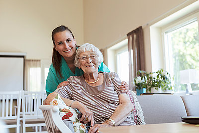 Portrait of smiling senior woman and healthcare worker at nursing home - p426m2072538 by Kentaroo Tryman