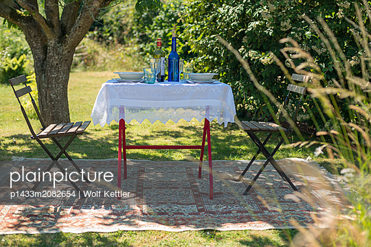 A table is set for two on a rug in a summer garden. - p1433m2082654 by Wolf Kettler